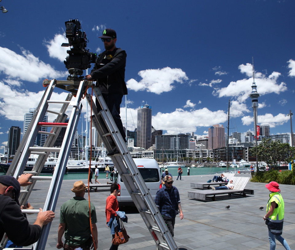 Camera man up a ladder filming a television show in Auckland city