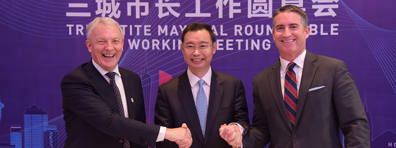 The three mayors of Auckland, Guangzhou and Los Angeles shake hands at a previous Tripartite Summit