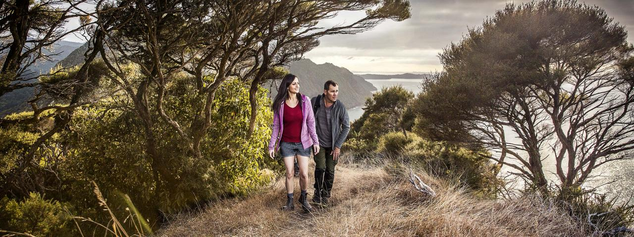 Couple hiking on a hilltop with sea in the background (credit: Todd Eyre)