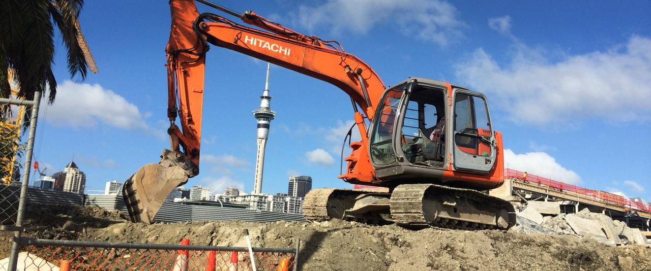 Digger with city in the background