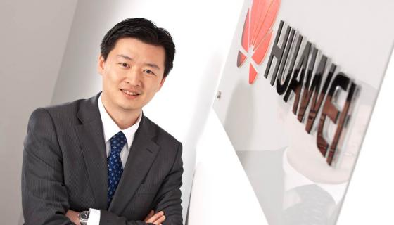 Man standing next to Huawei sign