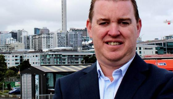 Man standing with Sky Tower in the background